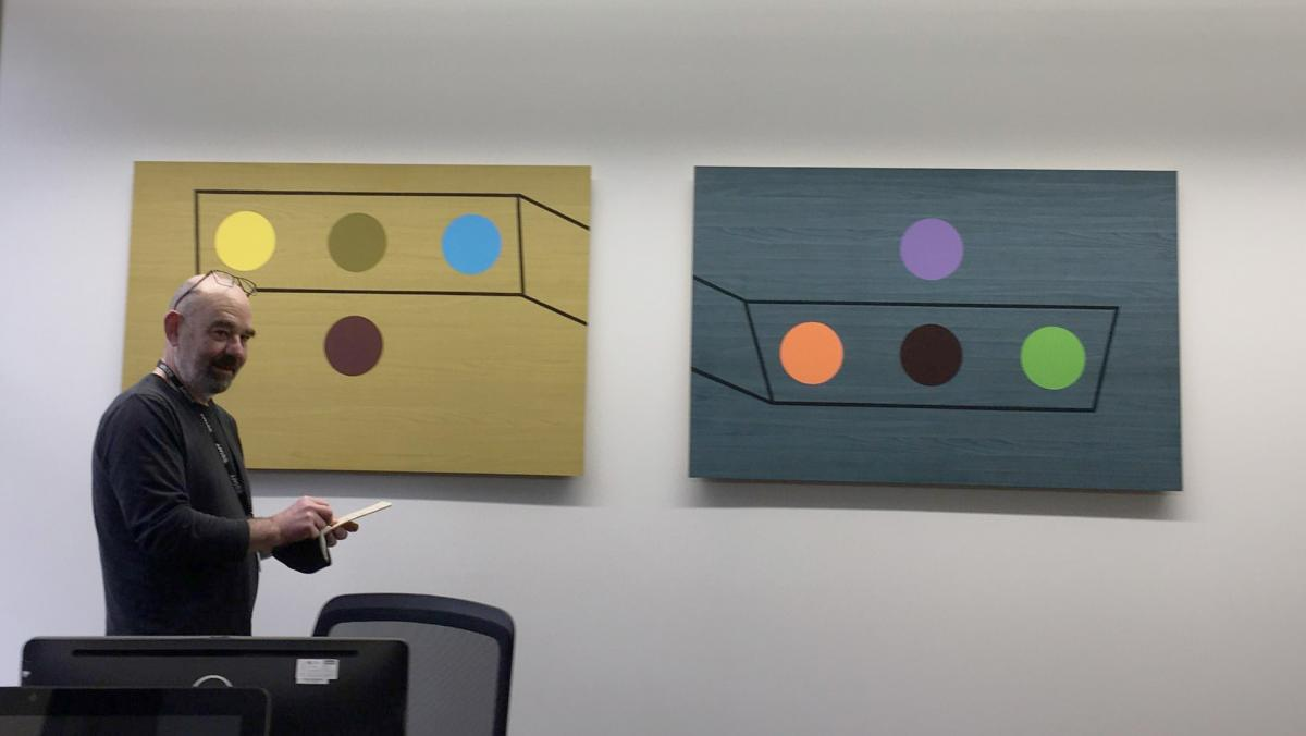 "A photograph of John Swarbrick installing his own artwork at IALS: ""Table 1 (Yellow) and Table 2 (Blue)"