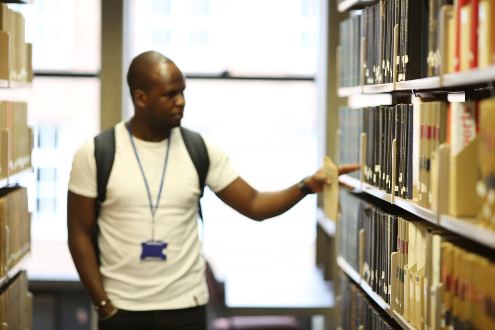Picture of student browsing for a book in IALS Library